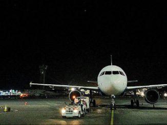 Avión esperando por la noche en el aeropuerto