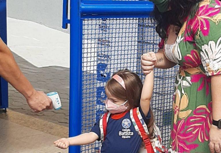 Toma de temperatura a una niña a la entrada de un colegio
